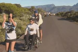 3 personnes participent à un marathon. L'une d'entrre elles est en fauteuil roulant