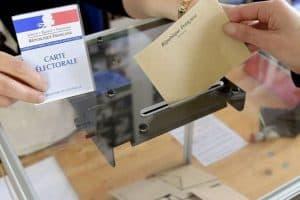 Photo d'une urne et d'un bulletin de vote. On aperçoit la carte éléctorale en arrière plan.