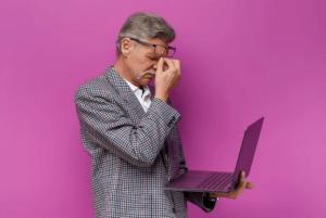 Un homme tient un ordinateur d'une main. Il place sa seconde main sur son visage en soulevant ses lunettes.