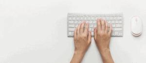 Photo de mains sur un clavier d'ordinateur. Une souris est à côté.